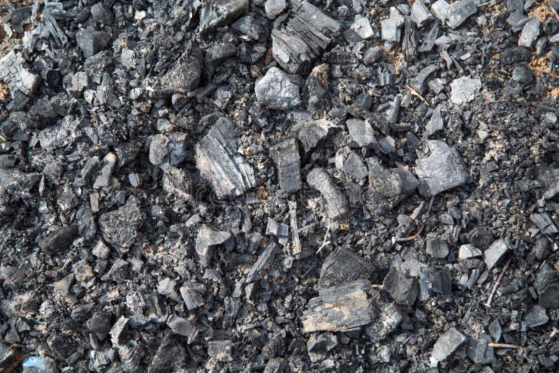 Vista di carbone che rimane dopo il fuoco, con i chiodi backgrounds immagine stock
