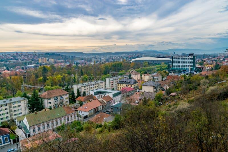 Vista di Cluj-Napoca dalla collina di Cetatuie con lo stadio a uso multiplo dell'arena di Cluj nei precedenti un giorno nuvoloso  immagine stock