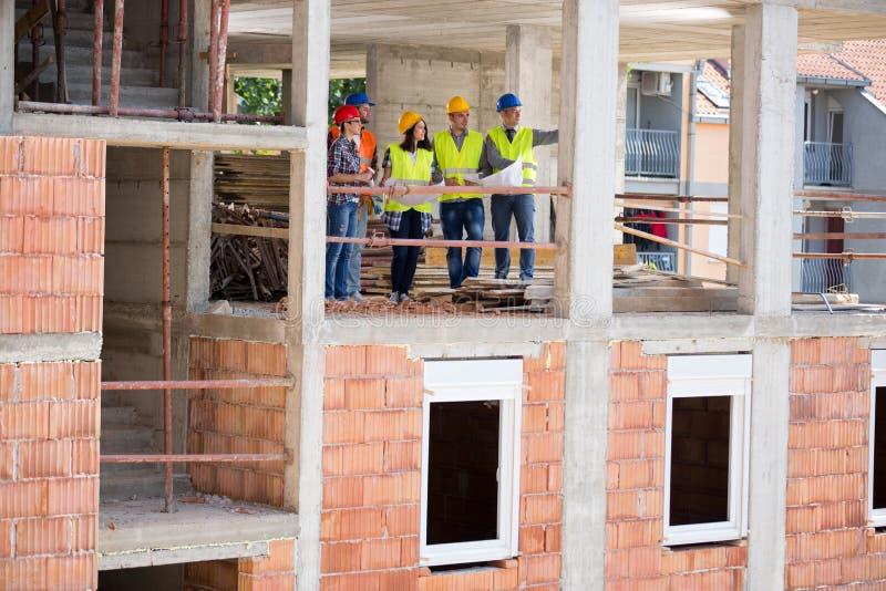Vista di costruzione in corso con il gruppo di architetti fotografia stock libera da diritti