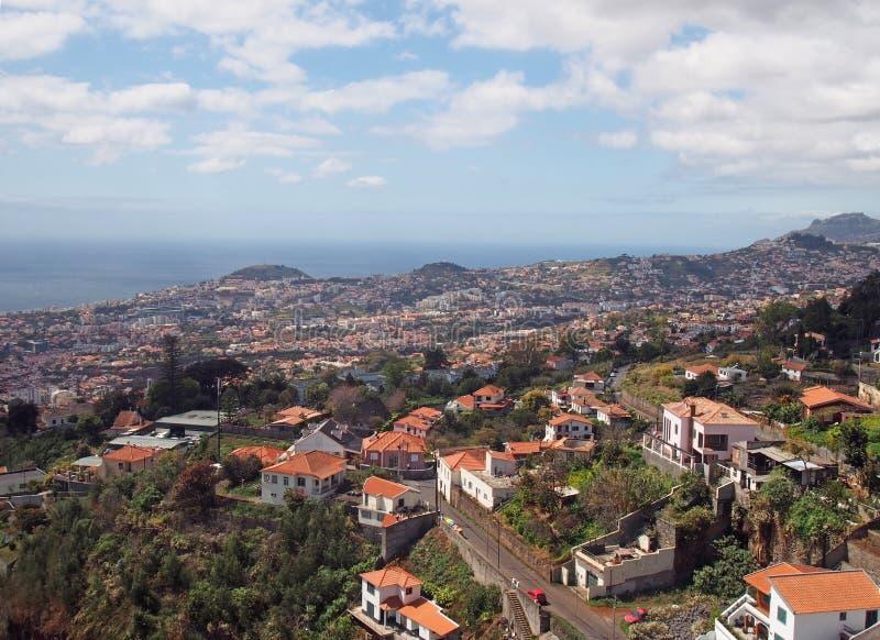 Vista di Funchal da sopra la mostra della città e le colline con l'oceano ed il cielo blu nella distanza fotografia stock libera da diritti