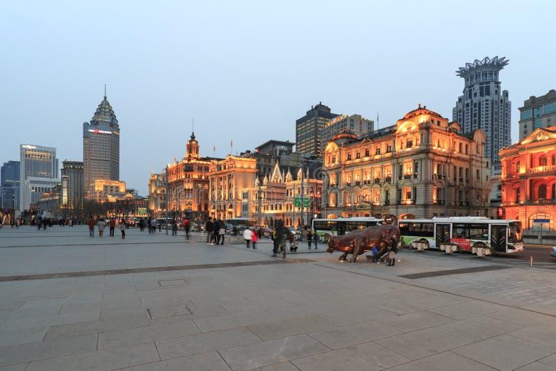 Vista di giorno di Bund di Shanghai ed il toro bronzeo ed alcuni turisti che passano vicino fotografia stock