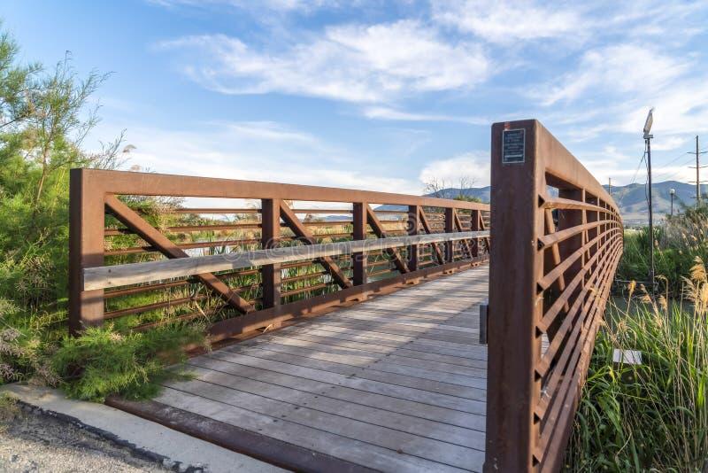 Vista di giorno soleggiato di un ponte con la guardavia di legno del metallo e della piattaforma sopra un lago immagine stock