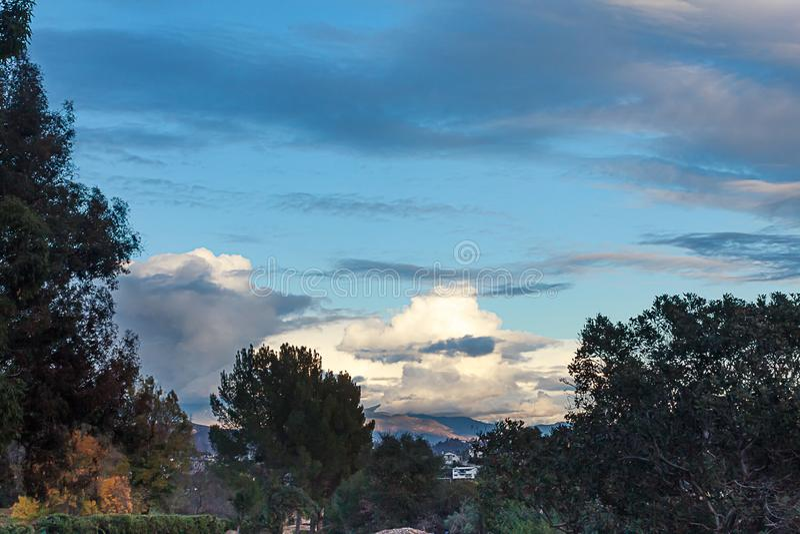 Vista di Hillside delle case con le montagne dei giardini e le grandi nuvole con legno di bosso e l'eucalyptus fotografia stock libera da diritti