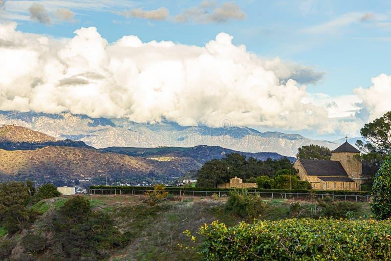 Vista di Hillside delle strade domestiche delle colline con il cloudscape delle montagne di San Gabriel, chiesa del mattone fotografie stock libere da diritti