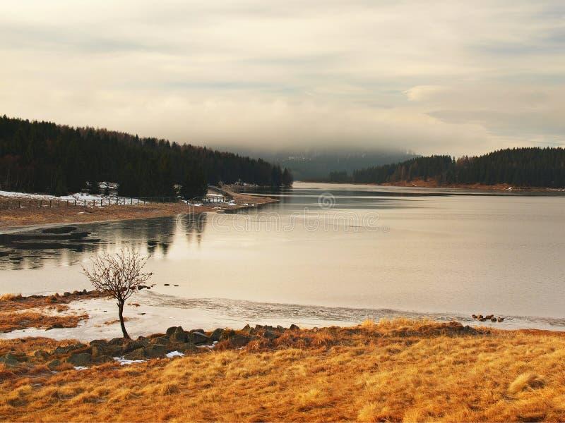 Vista di inverno sopra il lago con ghiaccio blu sottile alla banca opposta fotografia stock libera da diritti