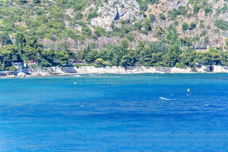 Vista di luce del giorno ad acqua blu con le boe, le costruzioni ed il mare gialli immagini stock libere da diritti