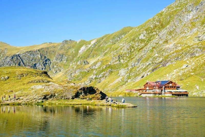 Vista di luce del giorno al cottage del lago Balea con le montagne verdi immagini stock libere da diritti