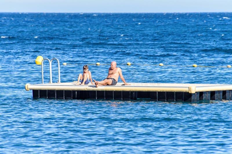 Vista di luce del giorno al padre ed al figlio che si siedono sul platfor di galleggiamento di nuotata fotografia stock libera da diritti