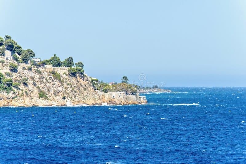 Vista di luce del giorno alla costa con le costruzioni ed all'acqua che spruzza le rocce fotografie stock