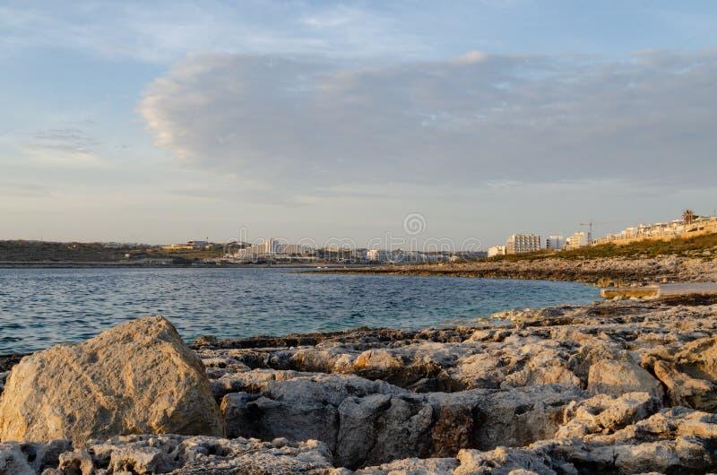 Vista di mattina di Buggiba Malta dalla roccia sul mare, alba fotografia stock libera da diritti