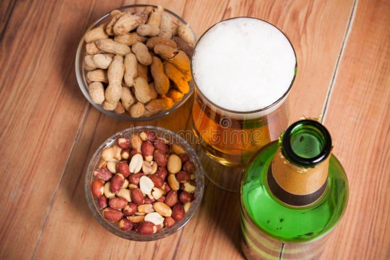 Vista di natura morta dell'angolo alto di vetro di birra inglese fredda, bottiglia di birra, immagine stock libera da diritti