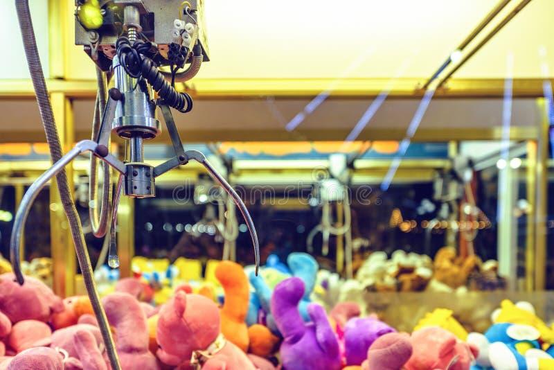 Vista di notte alla macchina dell'artiglio in pieno dei giocattoli molli variopinti fotografia stock