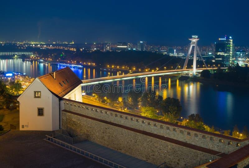 Vista di notte dal castello di Bratislava sul Danubio e sul ponte futuristico SNP immagini stock