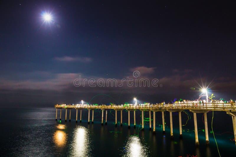 Vista di notte della spiaggia dell'oceano con il pescatore fotografie stock