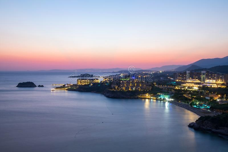 Vista di notte della spiaggia e degli hotel sulla costa dell'oceano o del mare fotografia stock libera da diritti