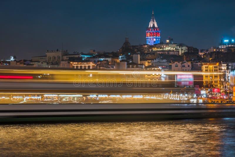 Vista di notte della torre di Galata di paesaggio urbano di Costantinopoli con fare galleggiare le barche turistiche in Bosphorus immagini stock libere da diritti