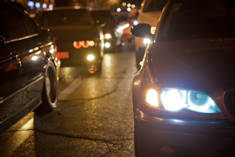 Vista di notte delle automobili Strada nella città alla notte con luce elettrica gialla e rossa per le automobili durante stanno  immagine stock