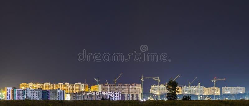 Vista di notte di panorama di molte gru della costruzione al cantiere fotografia stock