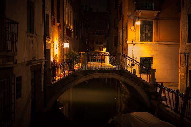 Vista di notte di Venezia con un piccolo ponte nella luce gialla delle lanterne fotografie stock
