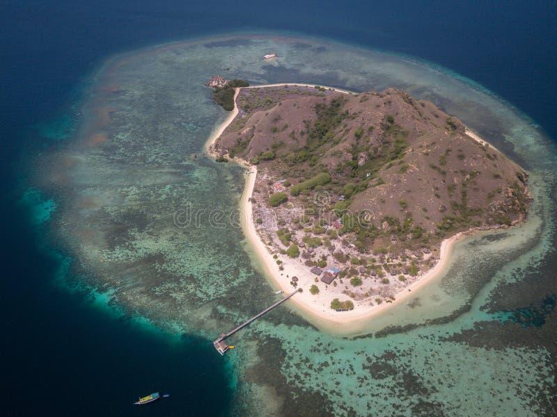 Vista di occhi di uccello dell'isola di Kanawa con il mare del turchese e le barche turistiche, Pasir Putih, Komodo, Manggarai ad fotografia stock libera da diritti