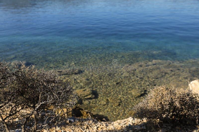 Vista di ora legale dalla spiaggia all'isola cristallina Grecia di Poros della baia di amore dell'acqua di mare fotografia stock