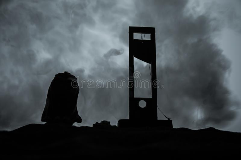 Vista di orrore della ghigliottina Primo piano di una ghigliottina su un fondo nebbioso scuro immagine stock