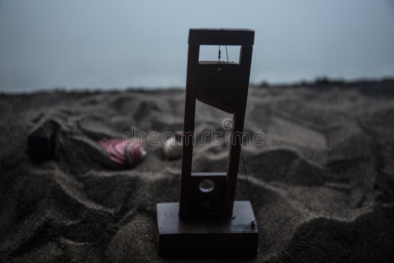 Vista di orrore della ghigliottina Primo piano di una ghigliottina su un fondo nebbioso scuro fotografia stock