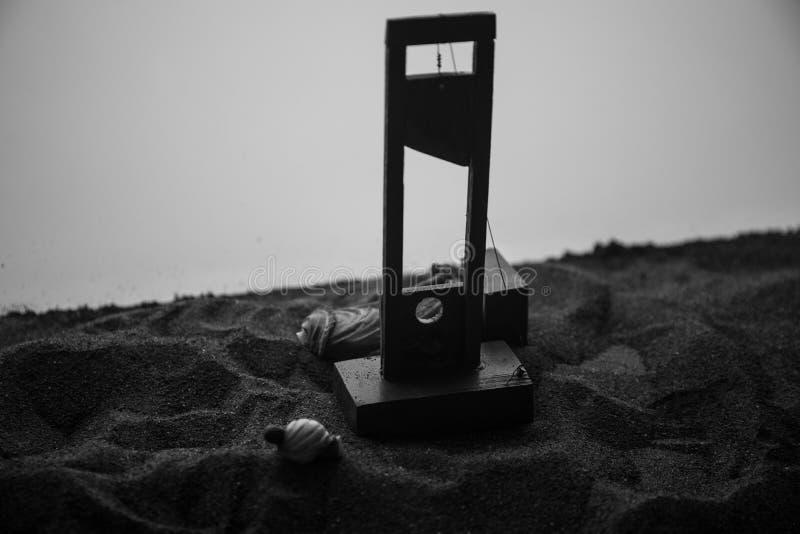 Vista di orrore della ghigliottina Primo piano di una ghigliottina su un fondo nebbioso scuro fotografia stock libera da diritti