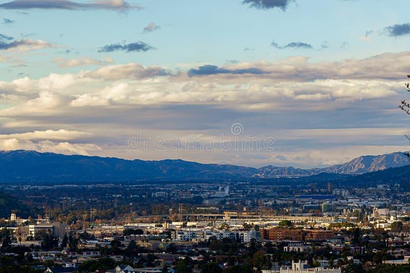 Vista di Panaramic dei commerci e delle case con le case del pendio di collina e delle montagne della città con cloudscape espans immagine stock