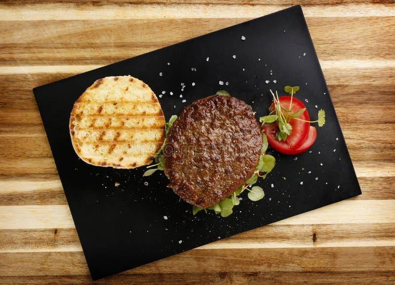 Vista di piano di un hamburger raro succulente e succoso del manzo, con il contorno del crescione e del pomodoro, in un panino de fotografie stock