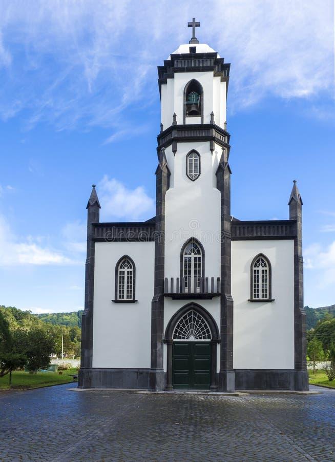 Vista di piccola chiesa bianca e grigia di sao Nicolau al villaggio di Sete Cidades sull'isola di sao Miguel, Azzorre fotografia stock