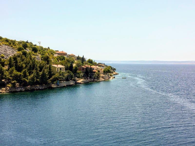 Vista di piccola città croata tradizionale lungo il mare adriatico incredibilmente bello mentre guidando la strada principale adr fotografia stock libera da diritti