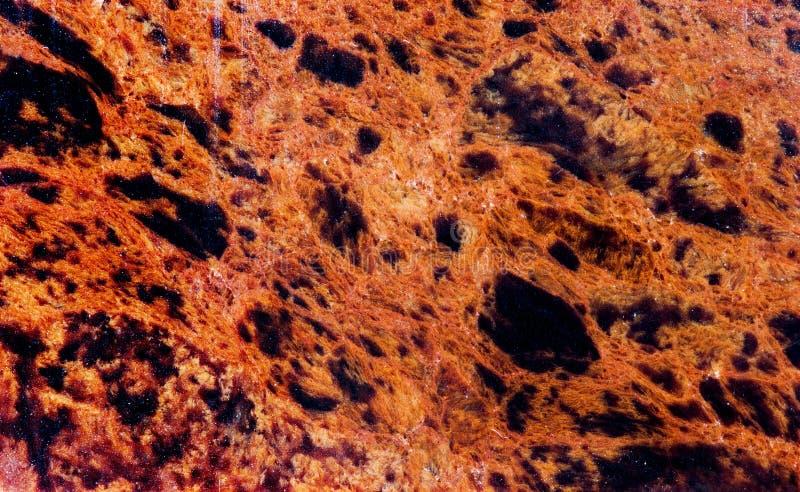 Vista di pietra minerale di macro del modello di struttura dell'ossidiana Bello marrone rosso scuro di vetro vulcanico con il fon fotografia stock