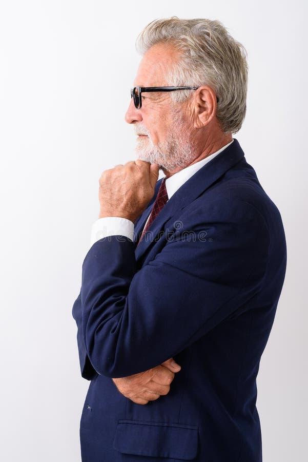 Vista di profilo del whi di pensiero dell'uomo d'affari barbuto senior bello fotografia stock libera da diritti