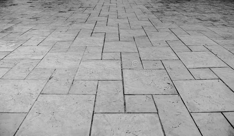 Vista di prospettiva del lerciume monotono Gray Brick Marble Stone incrinato sulla terra per la strada della via Marciapiede, str fotografie stock libere da diritti
