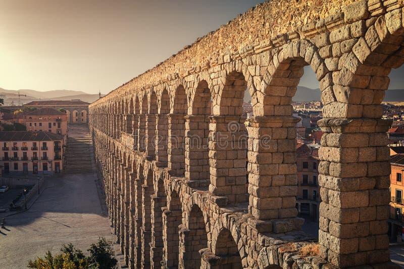 Vista di prospettiva dell'aquedotto romano della città di Segovia, accanto ad alcune case dell'agglomerazione urbana, Segovia, Sp immagine stock libera da diritti