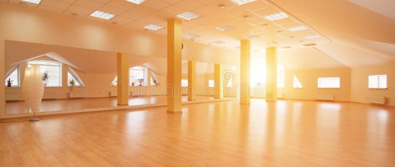 Vista di prospettiva dello studio soleggiato vuoto di yoga con la pavimentazione di legno immagine stock