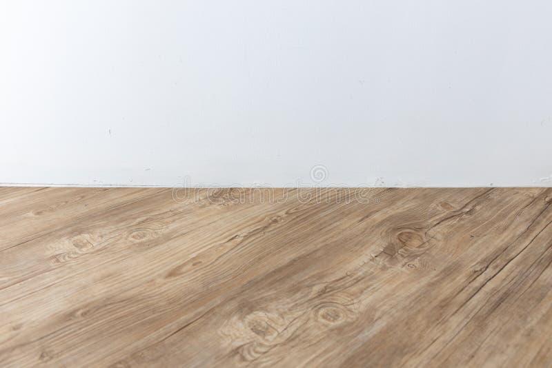 Vista di prospettiva di stanza interna vuota con la parete del cemento bianco ed il pavimento di legno marrone della spina di pes immagini stock