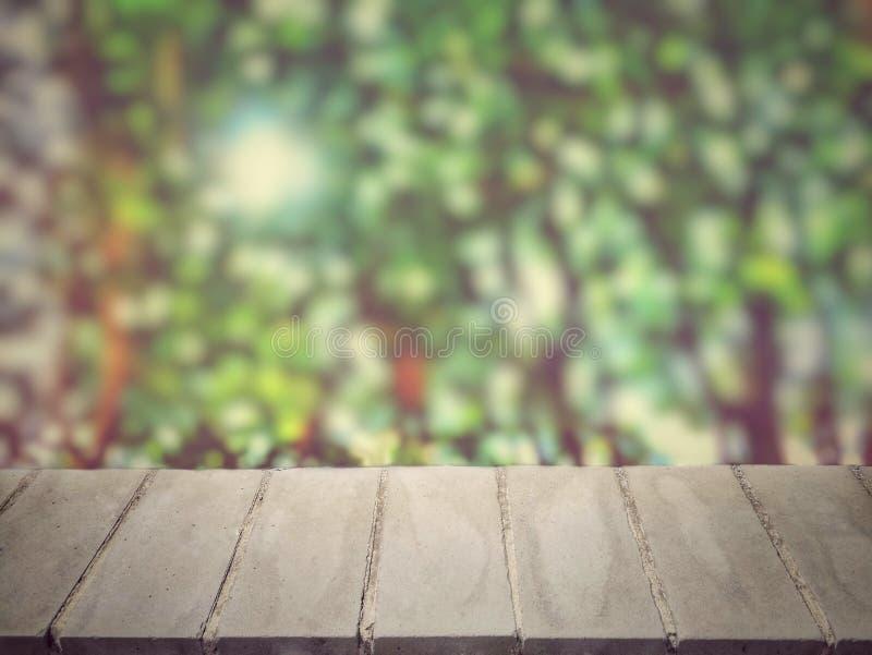 Vista di prospettiva di superficie di calcestruzzo vuota davanti al fondo vago degli alberi con luce solare fotografia stock libera da diritti