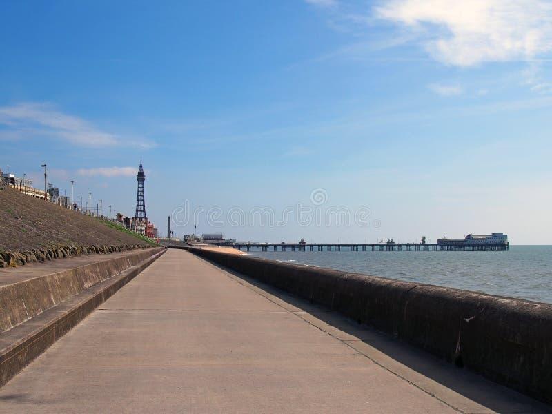 Vista di prospettiva verticale lungo la passeggiata pedonale a Blackpool con una vista della torre della città ed il pilastro nel fotografia stock