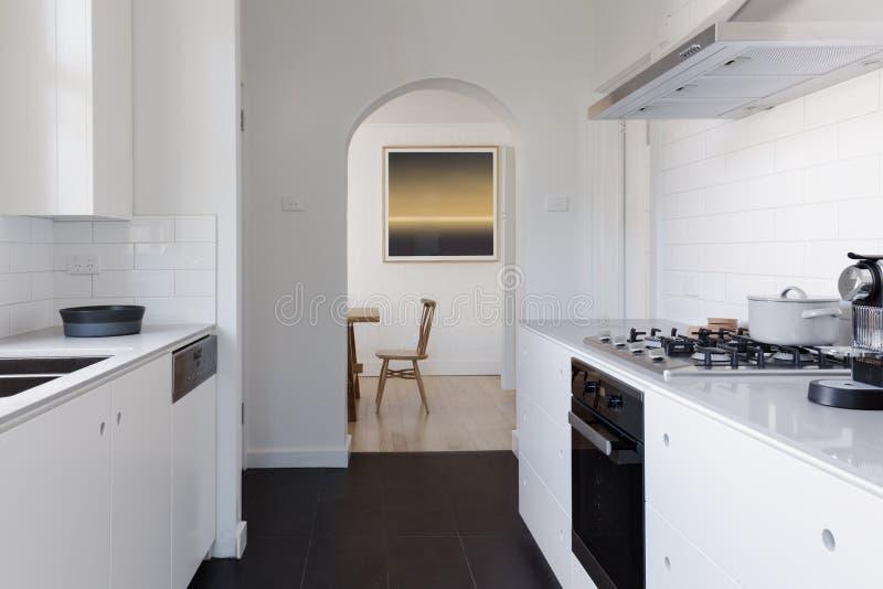 Vista di sala da pranzo alla conclusione di un ki bianco contemporaneo della cambusa fotografie stock