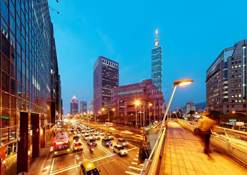 Vista di sera di una passerella pedonale sopra un angolo di strada affollata nella città di Taipei con la torre & il World Trade  immagini stock libere da diritti