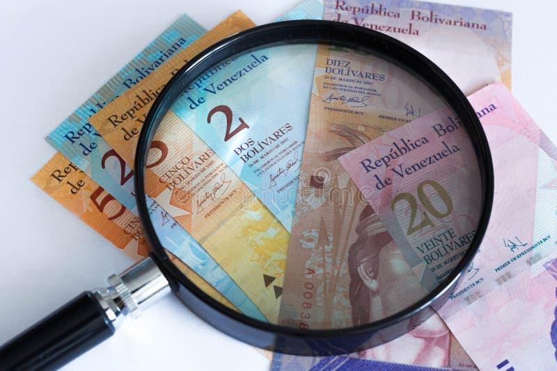 Vista di soldi venezuelani con la lente d'ingrandimento, concetto di crisi finanziaria immagini stock libere da diritti