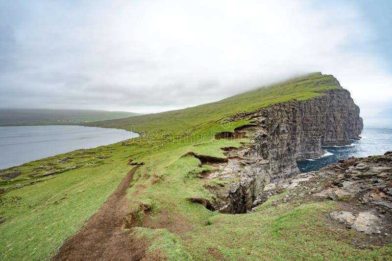 Vista di stupore del lago di illusione sulle montagne dello schiavo della scogliera ripida di Tralanipan nell'isola di Vagar, iso fotografie stock libere da diritti