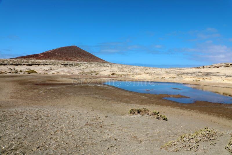 Vista di stupore del vulcano di Montana Roja con lo stagno nella riserva naturale del deserto della sabbia in EL Medano, Tenerife fotografie stock libere da diritti