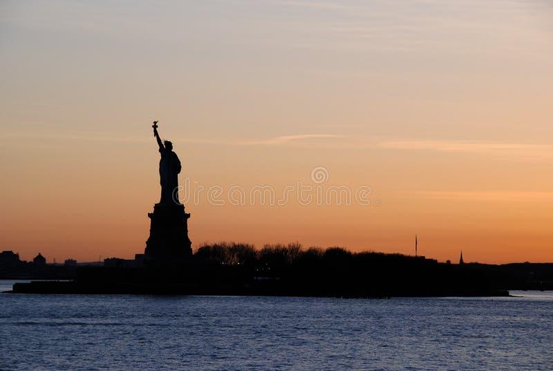 Vista di stupore dell'icona americana la statua della libertà, al tramonto Spazio per testo immagini stock libere da diritti