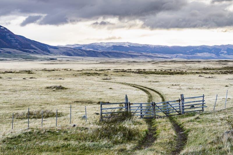 Vista di stupore della strada rurale nell'azienda agricola con il recinto e l'erba gialla bianca con fondo delle montagne della n fotografia stock libera da diritti