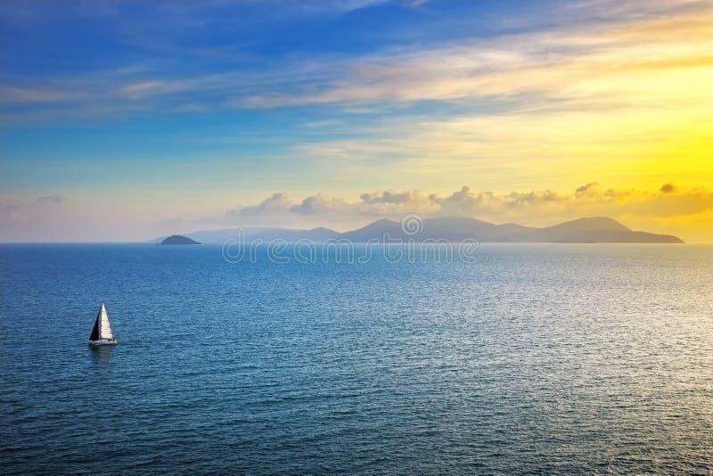 Vista di tramonto dell'isola di Elba da Piombino una barca a vela Mediterranea fotografia stock libera da diritti