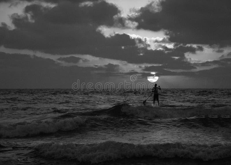 Vista di tramonto di estate di una spiaggia sotto un cielo nuvoloso con una singola siluetta del surfista del sup in bianco e ner fotografie stock libere da diritti