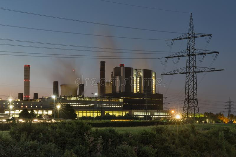 Vista di tramonto nella centrale elettrica con il pilone di elettricità in Germania fotografie stock libere da diritti